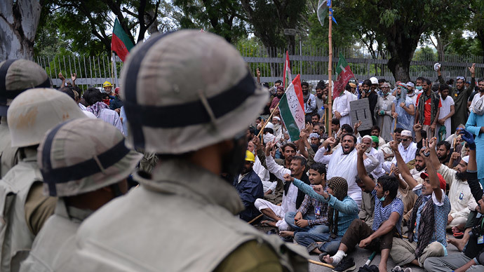 Pakistani soldiers stand guard as supporters of Canadian cleric Tahir ul Qadri and cricketer-turned politician Imran Khan shout anti-government slogans outside the prime minister's residence in Islamabad on September 1, 2014. (AFP Photo / Aamir Qureshi)