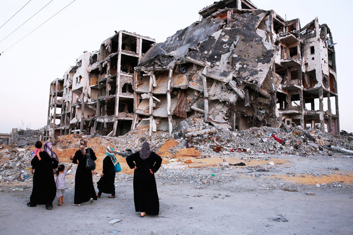Palestinian women look at the shattered remains of a building complex that was destroyed by fighting between Hamas Militants and Israel on August 29, 2014 in the northern Gaza Strip city of Beit Hanun.(AFP Photo / Roberto Schmidt)