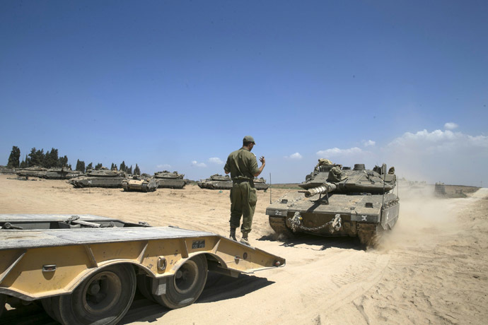 An Israeli soldier directs a tank onto a truck at a staging area near the border with the Gaza Strip August 27, 2014. (Reuters)