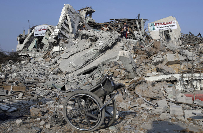 A wheelchair is seen as Palestinians stand atop the ruins of the headquarters of El-Wafa rehabilitation hospital, which witnesses said was destroyed during a seven-week Israeli offensive, in the east of Gaza City August 28, 2014. (Reuters)