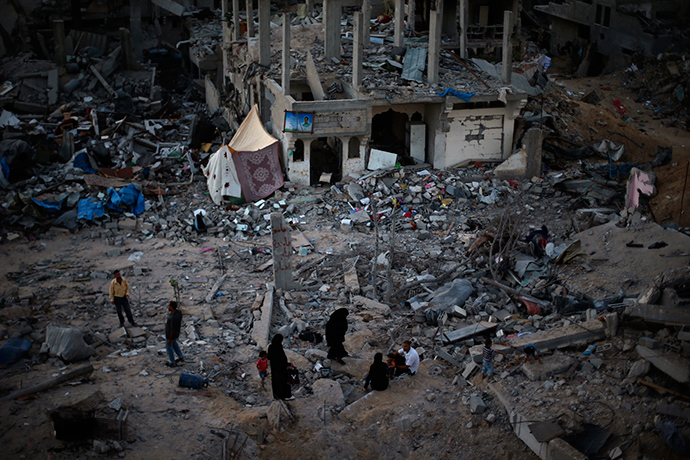 Palestinians sit atop the ruins of their house which witnesses said was destroyed during the Israeli offensive, in the east of Gaza City September 3, 2014 (Reuters / Suhaib Salem)