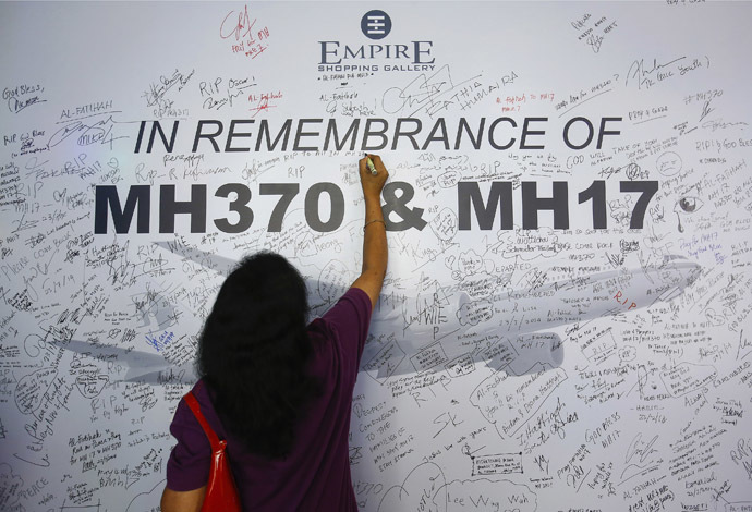 A woman writes a message on a dedication board for the victims of the downed Malaysia Airlines Flight MH17 airliner and the missing Flight MH370, in Subang Jaya outside Kuala Lumpur July 23, 2014. (Reuters)