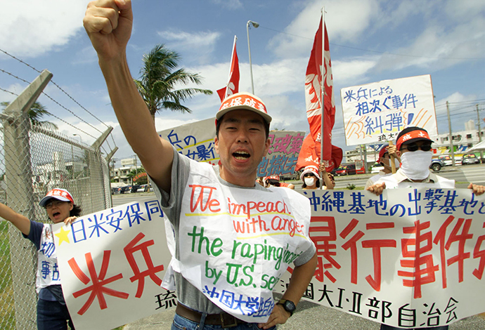 An Okinawan student raises his fists and shouts anti-U.S. slogans with his colleagues to protest the rape of a young Japanese woman and the U.S. miltary presence in Japan. (Reuters)