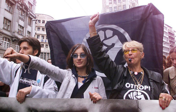 "Students and teachers parade under an ""Otpor"" (Resistance) movement flag, 09 October 2000 in Belgrade, during a demonstration against deputies of the Serbian Parliament who gathered for a meeting in the capital. (AFP Photo / Eric Cabanis)"