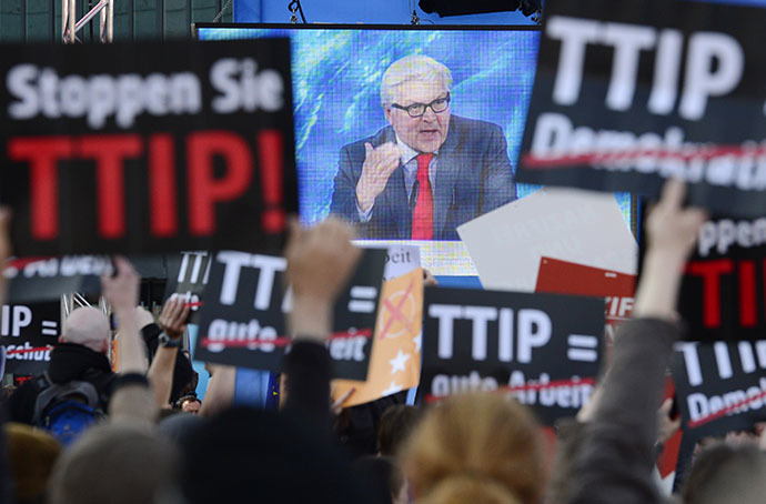 Protesters demonstrating against the Transatlantic Trade and Investment Partnership TTIP hold up signs in front of a screen showing German Foreign Minister Frank-Walter Steinmeier delivering a speech an election campaign meeting of the German Social Democratic Party for the upcoming European elections in Berlin, on May 19, 2014. (AFP Photo / John Macdougall)
