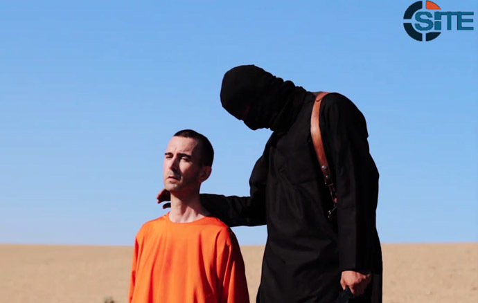 An image grab taken from a video released by the Islamic State (IS) and identified by private terrorism monitor SITE Intelligence Group on September 13, 2014 purportedly shows British aid worker David Haines dressed in orange and on his knees in a desert landscape speaking to the camera before being beheaded by a masked militant (R). (AFP Photo)