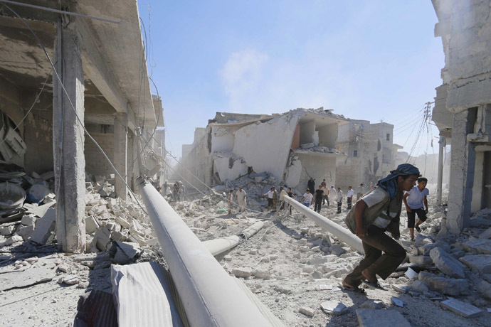 Residents inspect damage at a site hit by what activists said were barrel bombs dropped by forces of Syria's President Bashar al-Assad in the Ard Hamra district of Aleppo, September 20, 2014. (Reuters/Hosam Katan)