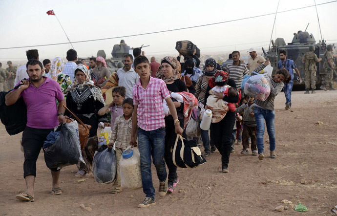 Syrian Kurds walk with their belongings after crossing into Turkey at the Turkish-Syrian border, near the southeastern town of Suruc in Sanliurfa province, September 20, 2014. (Reuters/Stringer)