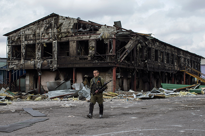 A rebel walks in front of a factory destroyed during recent shelling, in the town of Nizhnaya Krinka, eastern Ukraine, September 23, 2014 (Reuters / Marko Djurica)