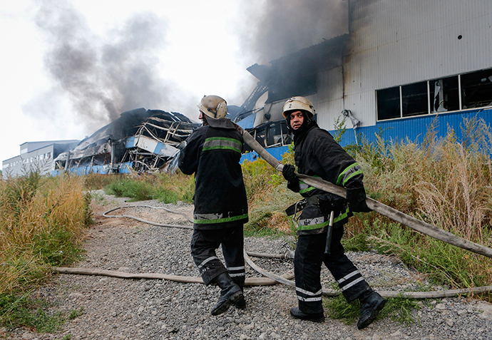 Firefighters pull a hose as they work to extinguish a fire at a printing factory hit by what locals say, was recent shelling by Ukrainian forces in Donetsk August 23, 2014 (Reuters / Maxim Shemetov)