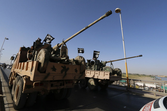 Militant Islamist fighters travel in a vehicle as they take part in a military parade along the streets of Syria's northern Raqqa province June 30, 2014. (Reuters/Striker)