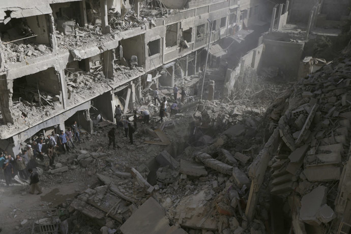 Residents inspect a damaged site after what activists say were four air strikes by forces loyal to Syria's President Bashar al-Assad in Douma, eastern al-Ghouta, near Damascus September 24, 2014. (Reuters/Bassam Khabieh)