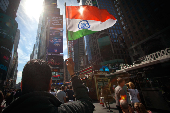 A man waves an Indian national flag as he assembles with a large crowd of people in Times Square to watch the speech by India's Prime Minister Narendra Modi simulcast on a giant screen in New York September 28, 2014. (Reuters / Carlo Allegri)