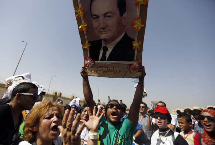 A supporter of former Egyptian President Hosni Mubarak holds his picture as he shouts slogans outside a police academy on the outskirts of Cairo September 27, 2014. (Reuters)