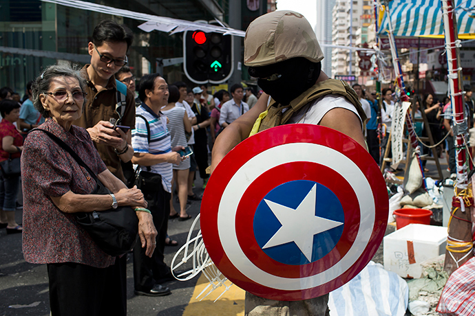 A protester of the Occupy Central movement carries a shield from the 'Captain America' comic book series as he stands on a main road at the Mong Kok shopping district in Hong Kong October 6, 2014 (Reuters / Tyrone Siu)