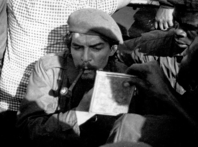"""Picture taken 21 November 1965 of Argentine-born guerrilla leader Ernesto """"Che"""" Guevara (aka Tatu -number 3 in swahili) shaving on board a barge while crossing the Tanganika Lake from the then Congo Leopoldville (Belgian Congo) to Tanzania, during the withdrawal of forces after a failed campaign in Congo. (AFP Photo)"""