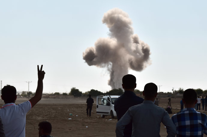 A Kurdish man flashes the V-sign for victory as smoke rises following an air strike on the western sector of the Syrian town of Ain al-Arab, known as Kobane by the Kurds, as seen from the Turkish-Syrian border, in the southeastern town of Suruc, Sanliurfa province, on October 8, 2014. (AFP Photo / Aris Messinis)