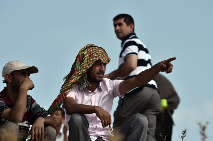 A Kurdish man gestures next to others as they watch fighting from a hill at the Turkish-Syrian border, in the southeastern Turkish village of Mursitpinar, Sanliurfa province, across from the Syrian town of Ain al-Arab, known as Kobane by the Kurds, on October 9, 2014. Turkish soldiers stand near a tank on a hill at the Turkish-Syrian border, in the southeastern Turkish village of Mursitpinar, Sanliurfa province, across from the Syrian town of Ain al-Arab, known as Kobane by the Kurds, on October 9, 2014. (AFP Photo / Aris Messinis)
