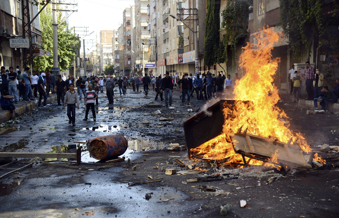 Kurdish protesters set fire to a barricade set up to block the street as they clash with riot police in Diyarbakir October 7, 2014. (Reuters/Stringer)