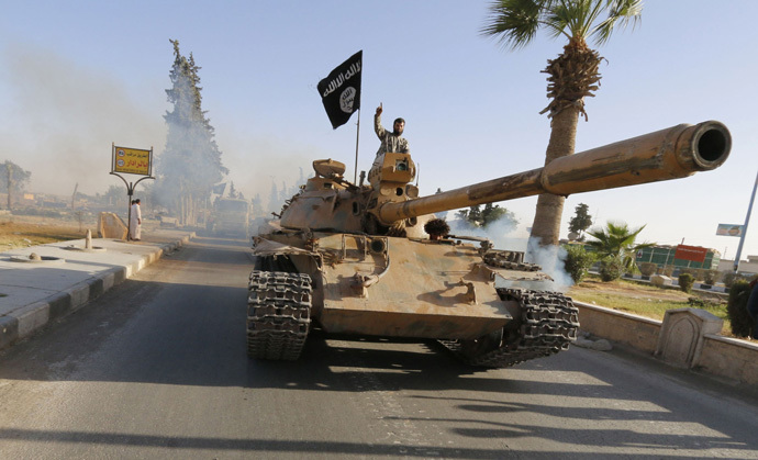Militant Islamist fighters on a tank take part in a military parade along the streets of northern Raqqa province June 30, 2014. (Reuters/Stringer)