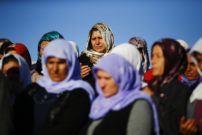 Turkish Kurdish women mourn during the funeral of Kurdish fighters killed during clashes against Islamic State in Kobani, at a cemetery in the southeastern town of Suruc, Sanliurfa province October 21, 2014. (Reuters/Kai Pfaffenbach)