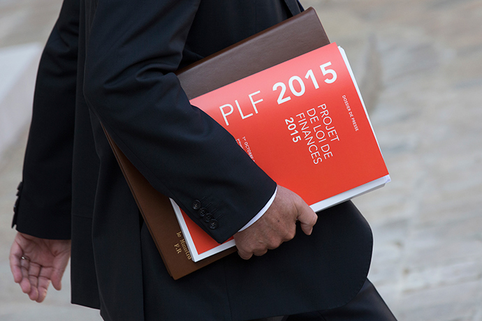 A government member holds a press release of France's 2015 Budget Project as he leaves following the weekly cabinet meeting at the Elysee Palace in Paris, October 1, 2014 (Reuters / Philippe Wojazer)
