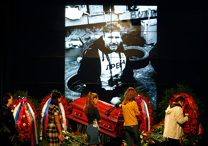 People walk past a coffin with the body of Russian photojournalist Andrey Stenin during a memorial service in Moscow, September 5, 2014 (Reuters / Sergey Karpukhin)