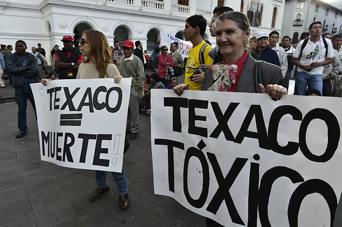 "Activists holds signs reading ""Texaco = Death"" and ""Texaco = Toxic"" as they protest against US multinational energy corporation Chevron at a square in Quito on May 21, 2014. (AFP Photo/Rodrigo Buendia)"