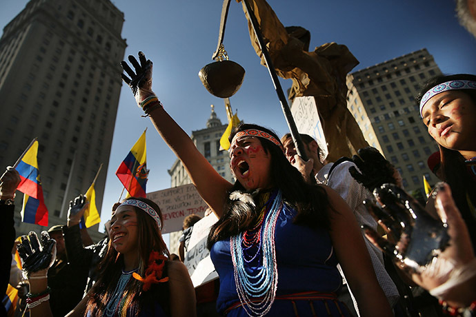 Following an $18 billion judgment against Chevron from a court in Ecuador, protesters, some in traditional dress and with black hands representing oil, demonstrate in front of a United States courthouse against the Chevron Corp on October 15, 2013 in New York City. (AFP Photo/Spencer Platt)