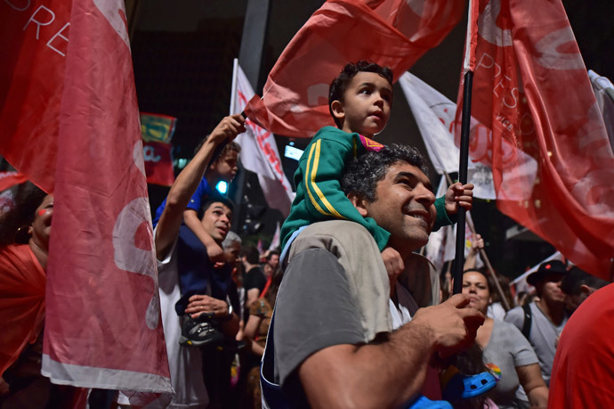 Supporters celebrate the reelection of the Brazilian President and presidential candidate for the Workers' Party (PT) Dilma Rousseff in the presidential election run-off along Paulista Avenue in Sao Paulo Brazil on October 26 2014. (AFP Photo / Nelson Almeida)
