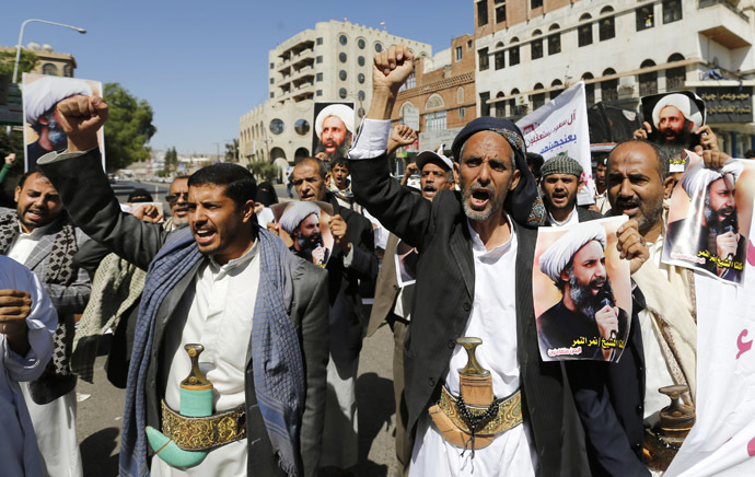 Shi'ite protesters shout slogans as they hold posters of Sheikh Nimr al-Nimr during a demonstration outside the Saudi embassy in Sanaa October 18, 2014. (Reuters/Khaled Abdullah)