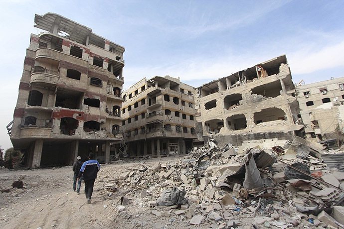 Civilians walk past damaged buildings in the Damascus suburb of Jobar October 28, 2014. (Reuters/Badra Mamet)