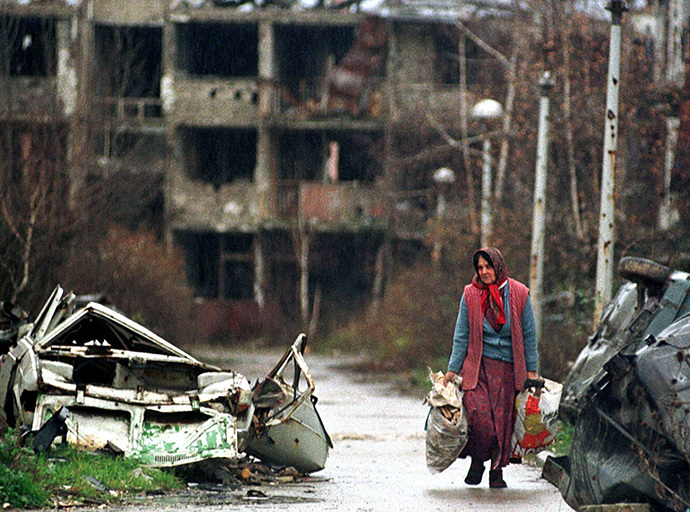An elderly woman carries her belongings November 22 in Sarajevo's war shattered airport settlement. (Reuters)