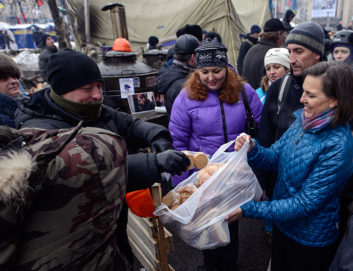A handout picture released on December 10, 2013 by Ukrainian Union Opposition press services hows US Assistant secretary of State for European and Eurasian Affairs Victoria Nuland (R) distributing cakes to protesters on the Independence Square in Kiev on December 10, 2013. (AFP Photo / Party Press-Service / Andrew Kravchenko)