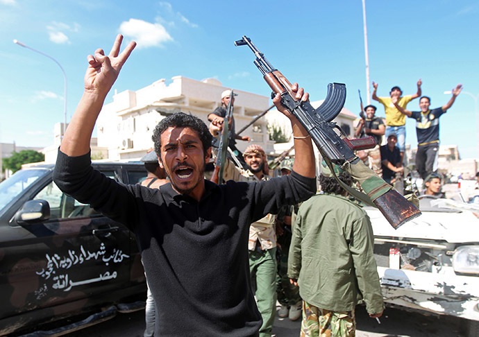 Libyan National Transitional Council (NTC) fighters celebrate in the eastern coastal city of Sirte following news of Moamer Kahdafi's capture and death on October 20, 2011.(AFP Photo/Ahmad Al-Rubaye)