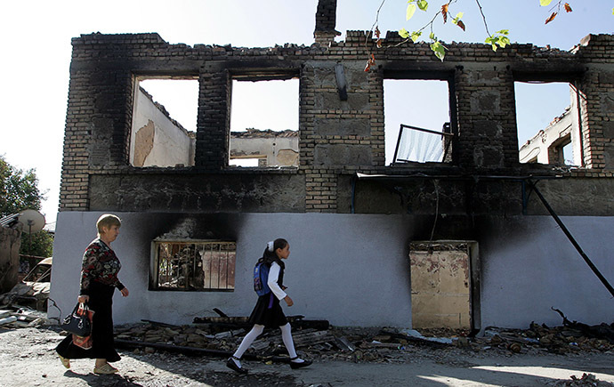 Ossetian people pass by a ruined house in Tskinvali. (AFP Photo/Kazbek Basayev)