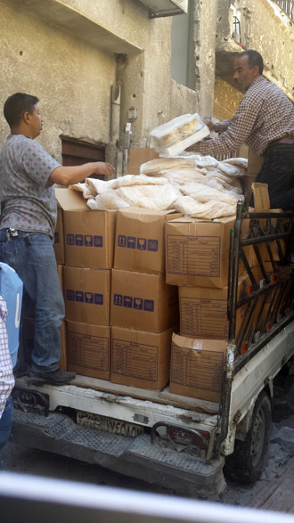 A small UNRWA van delivers boxes of staple foods to Yarmouk camp residents who wait at a pick-up point. Bread donated by the Syrian government lies atop the boxes.