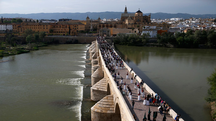 "Penitents walk during a procession of the ""La Vera-Cruz"" brotherhood during Holy Week, on the Roman Bridge near the Mosque of Cordoba, southern Spain, April 14, 2014.(Reuters / Javier Barbancho)"