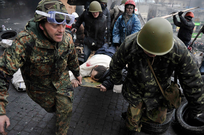 Protesters carry a wounded protester during clashes with poliсe, after gaining new positions near the Independence square in Kiev on February 20, 2014. (AFP PHhoto / Louisa Gouliamaki)