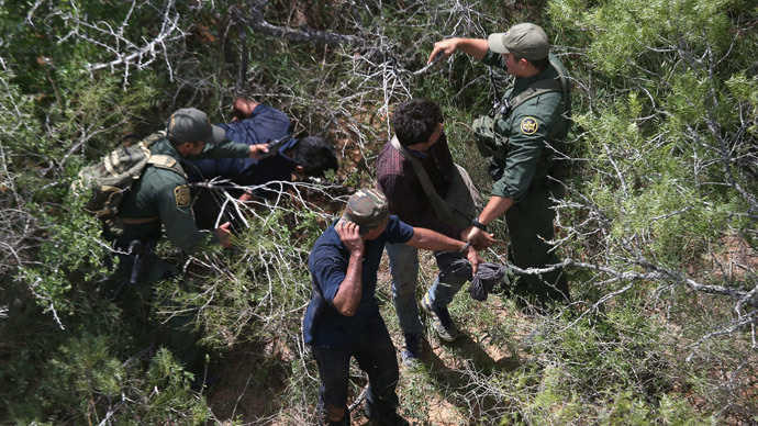 U.S. Border Patrol agents detain undocumented immigrants in the brush on September 11, 2014 near Falfurrias, Texas.(AFP Photo / John Moore)