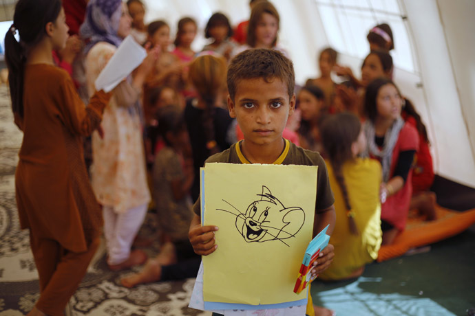 A displaced Iraqi child, who fled from the violence in Mosul by the Islamic State (IS), displays his drawing during refresher courses at the start of a school year organized by UNICEF at Baherka refugee camp in Erbil September 11, 2014. (Reuters/Ahmed Jadallah)