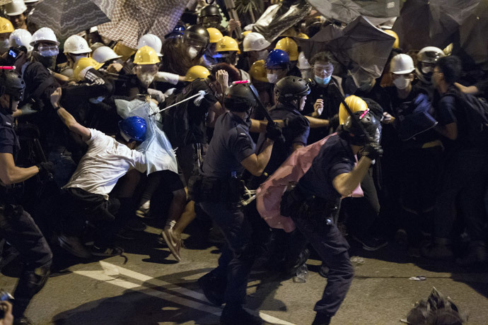 Police use batons against pro-democracy protesters near the government headquarters in the Admiralty district of Hong Kong on December 1, 2014. (AFP Photo / Dale de la Rey)