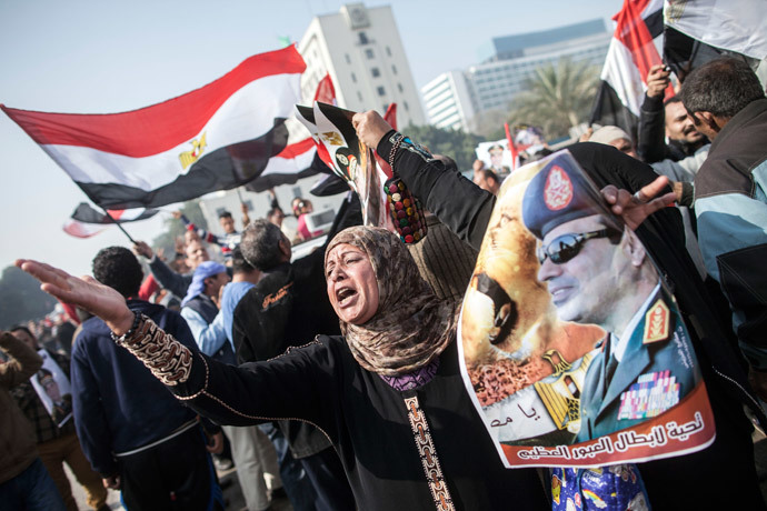 An Egyptian supporter of the military-installed government holds a poster bearing a portrait of General Abdel Fattah al-Sisi as she takes part in a rally marking the anniversary of the 2011 Arab Spring uprising in downtown Cairo on January 25, 2014. (AFP Photo / Mahmoud Khaled)