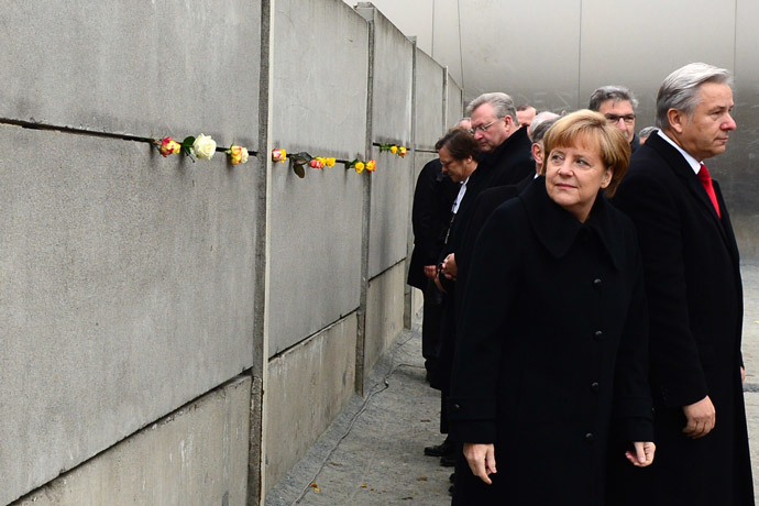 German Chancellor Angela Merkel (2ndR) and Berlin Mayor Klaus Wowereit (R) leave after putting roses in a preserved segment of the Berlin Wall during the commemorations to mark the 25th anniversary of the fall of the Berlin Wall at the Berlin Wall Memorial in the Bernauer Strasse in Berlin, on November 9, 2014. (AFP Photo / John Macdougall)