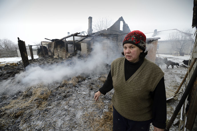 A woman stands by her smoldering home in the Lidievka district, after it was hit and destroyed by shelling in the eastern Ukrainian city of Donetsk on December 6, 2014. (AFP Photo/Eric Feferberg)