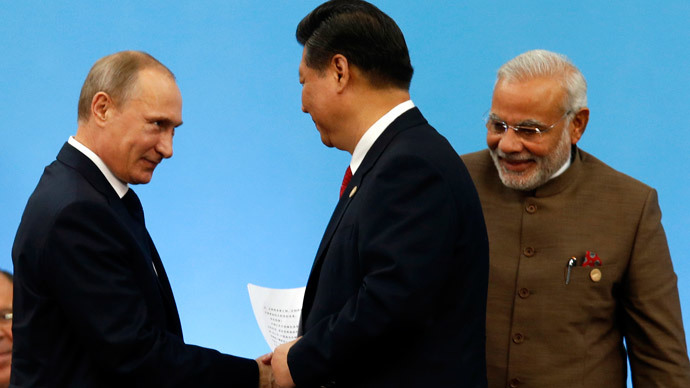 Russia's President Vladimir Putin (L) shakes hands with China's President Xi Jinping as India's Prime Minister Narendra Modi (R) looks on during the VI BRICS Summit in Fortaleza July 15, 2014.(Reuters / Paulo Whitaker)