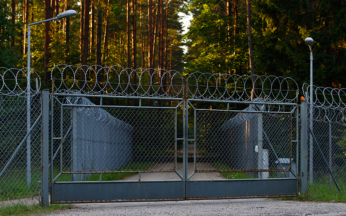 A car drives past barbed wire fence surrounding a military area in the forest in Stare Kiejkuty village, close to Szczytno in northeastern Poland (Reuters / Kacper Pempel)
