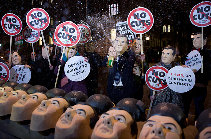 Anti-austerity protesters wearing masks of British Chancellor George Osborne, hold placards and chant slogans outside 10 Downing Street in central London on December 2, 2014, on the eve of the autumn statement (AFP Photo / Justin Tallis)