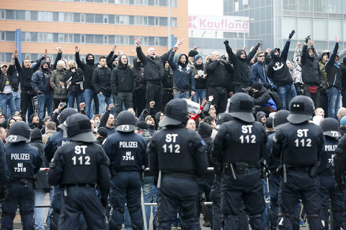 German riot police officers face protesters during a demonstration by neo-Nazis and self-styled soccer hooligans against ultra-conservative Islamic Salafists in Hanover November 15, 2014. (Reuters/Fabrizio Bensch)