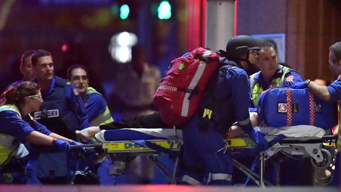 Australian paramedics work on an injured hostage as hostages are carried out of a cafe in the central business district of Sydney on December 16, 2014. (AFP Photo)